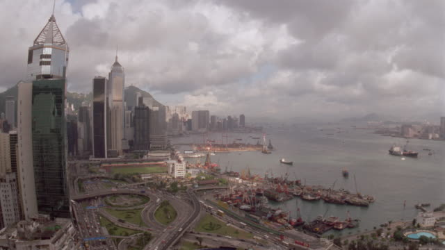 high angle of time lapse clouds over city with traffic and harbor with boats / victoria harbor / hong kong - anno 1997 video stock e b–roll