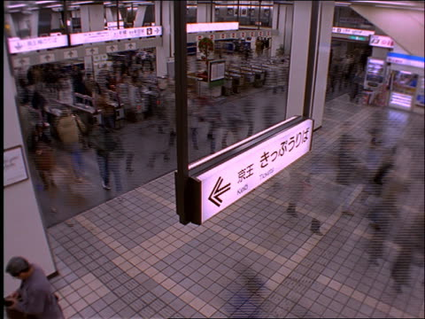 high angle of time lapse crowds + turnstiles in subway station / shinjuku / tokyo - 1997 stock videos and b-roll footage
