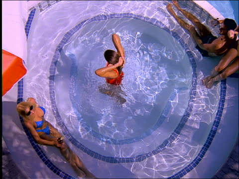 high angle of woman walking out of jacuzzi with people in it