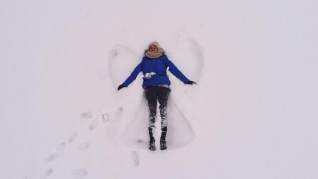 hög vinkel av unga kaukasiska kvinna att göra snöängel - ängel bildbanksvideor och videomaterial från bakom kulisserna