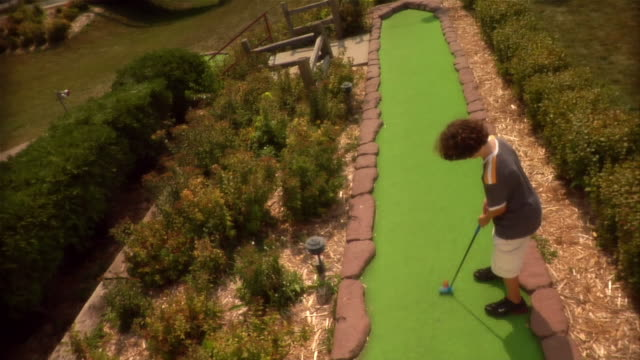 high angle over boy making fairway shot on mini golf course / missing shot and walking up fairway to retrieve ball - minigolf stock-videos und b-roll-filmmaterial