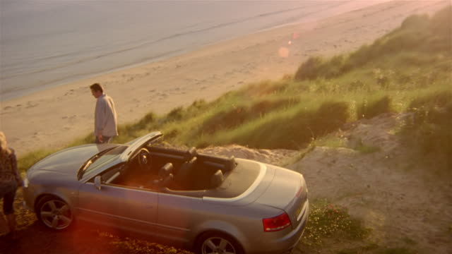 High angle over couple getting out of convertible parked on cliff over beach / sitting down and looking at view