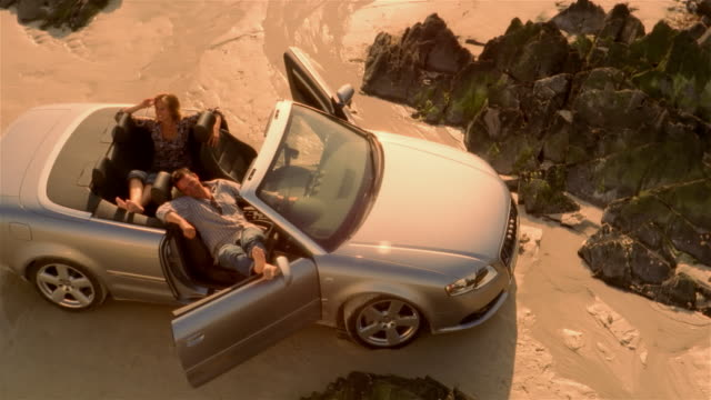 high angle over couple lounging in convertible car parked on beach - sonnenbaden stock-videos und b-roll-filmmaterial