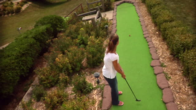 High angle over woman making fairway shot on mini golf course / missing shot and walking up fairway to retrieve ball