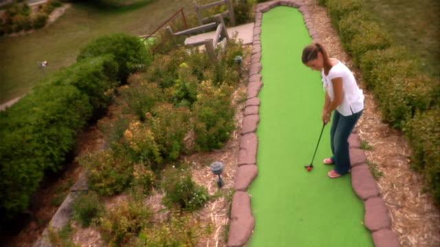 high angle over woman making fairway shot on mini golf course / walking down fairway after making shot - minigolf stock-videos und b-roll-filmmaterial