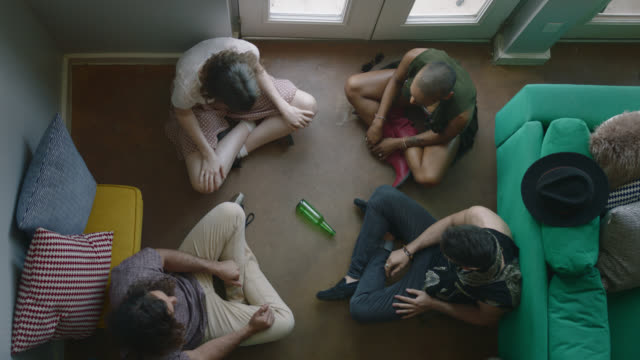 high angle overhead shot of four young people playing spin the bottle as two friends jokingly kiss. - spinning stock videos & royalty-free footage