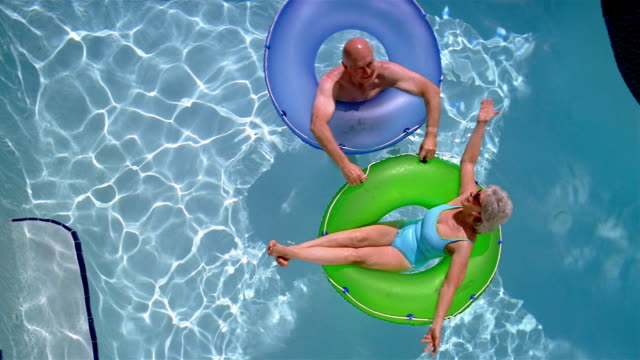 High angle overhead shot of senior couple floating on inner tubes in swimming pool
