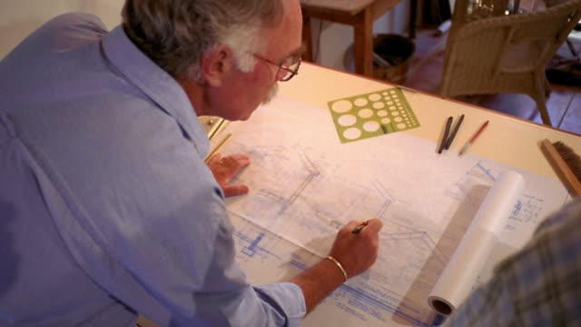 vídeos de stock, filmes e b-roll de high angle ms over-the-shoulder middle aged man + younger man talking + examining blueprint on drafting table - prancheta