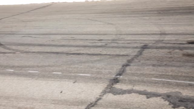 high angle pan across tire marks at a race track. - tire track stock videos & royalty-free footage