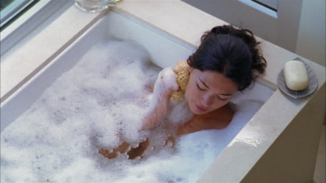 high angle pan asian woman in bathtub using sponge and washing her neck in bathtub - bubble bath stock videos and b-roll footage