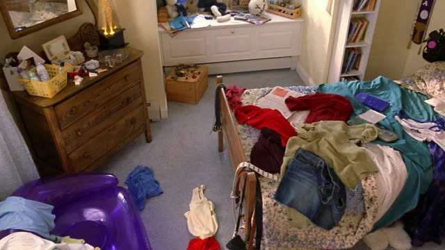 high angle pan messy bedroom with clothes lying on bed and floor - unordentlich stock-videos und b-roll-filmmaterial