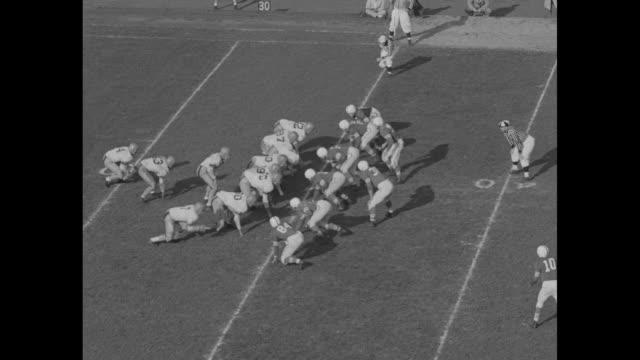 vídeos de stock e filmes b-roll de high angle pan of marching band spelling out hello / 2nd quarter ohio state richard widdoes quarterback intercepts minnesota pass scores touchdown /... - terceiro quarto de tempo