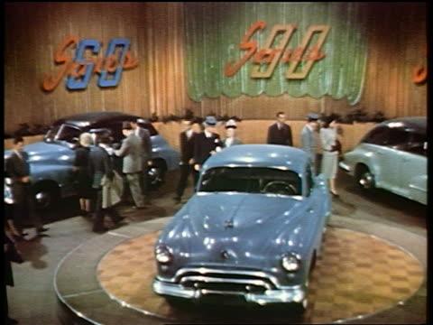 1948 high angle pan people looking at oldsmobiles on display in showroom / industrial - automobile industry stock videos & royalty-free footage