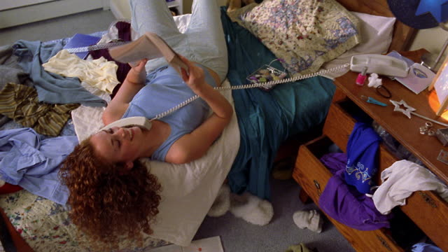 vidéos et rushes de high angle pan teen girl lying on messy bed, reading book and talking on telephone - messy bedroom