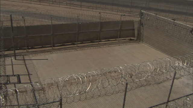 high angle pan-left - a water cannon faces a prison yard with a barbed-wire fence in california. / california, usa - prison wall stock videos & royalty-free footage