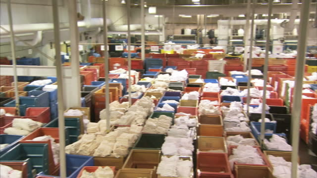 high angle pan-left - linens fill bins in an industrial laundry / las vegas, nevada - launderette stock videos and b-roll footage