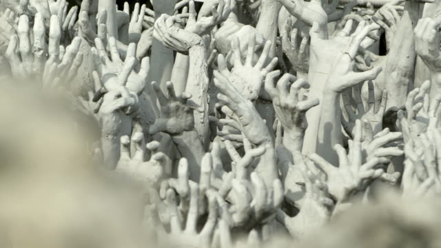 high angle panning shot of white hand sculptures at famous buddhist temple on sunny day - chiang rai, thailand - buddismo video stock e b–roll