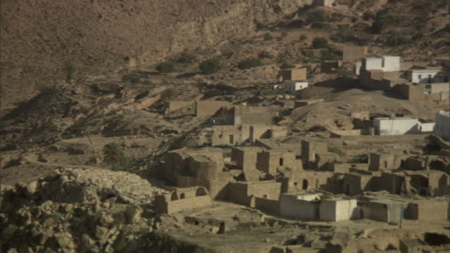 vídeos de stock, filmes e b-roll de high angle pan-right - houses surround a tall white steeple in a tunisian village in the great rift valley. / tunisia - cidade pequena