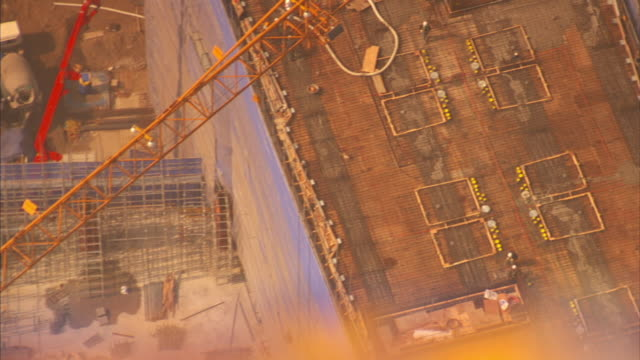 stockvideo's en b-roll-footage met high angle pan-right rack-focus tilt-down - concrete and steel form a foundation at a new songdo city construction site. / seoul, south korea - incheon