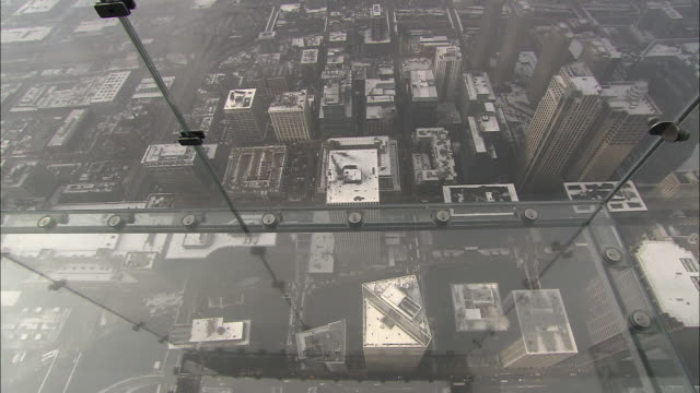 high angle pan-right tilt-up - chicago downtown rooftops appear through the glass floor and walls of a viewing platform on the sears tower. / chicago, illinois, usa - willis tower stock videos and b-roll footage