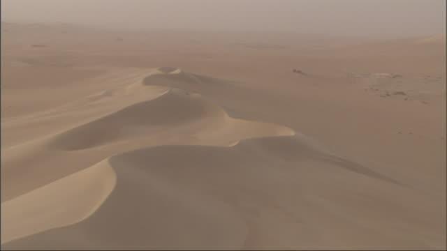 high angle, pan-right tracking-left - sand dunes spread across the sahara desert in egypt - ägypten stock-videos und b-roll-filmmaterial