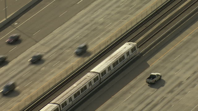 High Angle pan,right zoom,in , A commuter train speeds along the center of a divided freeway. / California