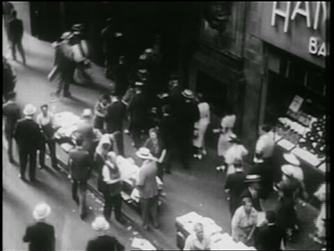 vidéos et rushes de b/w 1939 high angle pedestrians on sidewalk entering building + newspaper vendors / nyc / documentary - kiosque à journaux