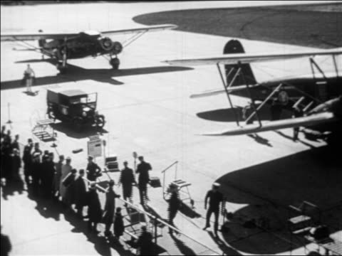 vídeos y material grabado en eventos de stock de b/w 1933 high angle people at gate + walking towards american airlines prop planes on airfield / industrial - 1933
