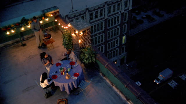 High angle people grilling and sitting at dinner table on rooftop w/buildings in background / NYC