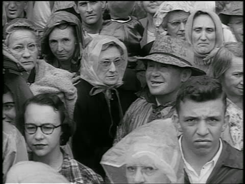b/w 1952 high angle people in crowd in rain / couple laughs / eisenhower whistlestop campaign / newsreel - anno 1952 video stock e b–roll