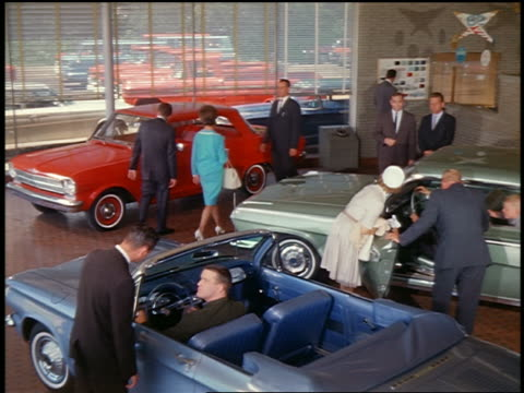 1962 high angle people looking at various chevrolet cars in showrooms with salesmen / industrial - autohandlung stock-videos und b-roll-filmmaterial