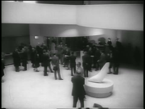 high angle people near door in lobby of guggenheim museum / nyc / newsreel - 1959 stock-videos und b-roll-filmmaterial