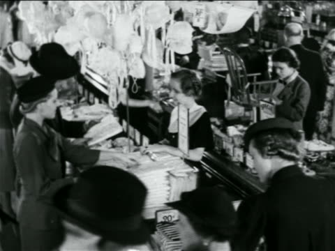b/w 1938 high angle people shopping at counters in crowded 5 and 10 store / industrial - discount shop stock videos & royalty-free footage