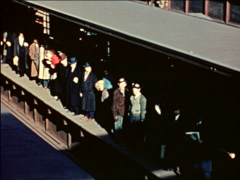 1941 high angle people waiting on platform of elevated train / Chicago / industrial