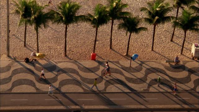 high angle people walking along boardwalk at copacabana beach / rio de janeiro - copacabana stock videos & royalty-free footage