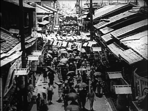 vídeos de stock, filmes e b-roll de b/w 1923 high angle people walking with parasols on tokyo street / japan / newsreel - 1923