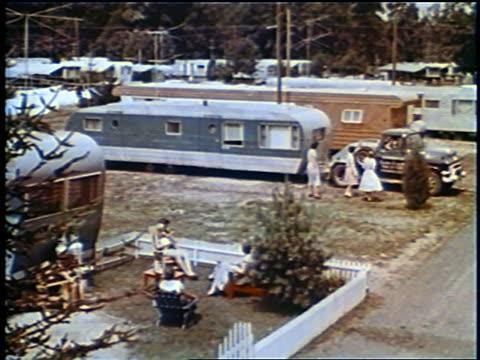 stockvideo's en b-roll-footage met 1958 high angle people waving to truck pulling trailer home leaving trailer park / florida / newsreel - aanhangwagen