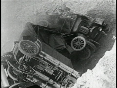 b/w 1925 high angle pile of crashed cars with spinning wheels in bottom of pit / feature - 1925 stock videos & royalty-free footage