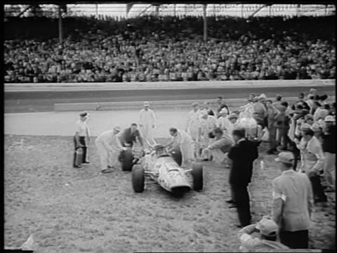 vidéos et rushes de b/w 1966 high angle pit crew surrounding graham hill in race car after winning indianapolis 500 / newsreel - graham hill