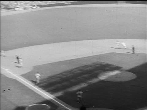 vídeos de stock e filmes b-roll de b/w 1955 high angle pan players throwing ball runner returning to first base / world series / nyc - camisola de basebol