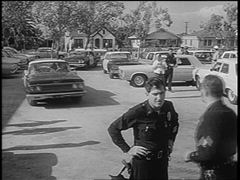 B/W 1965 high angle policemen talking squad cars in parking lot after Watts race riots low angle / newsreel