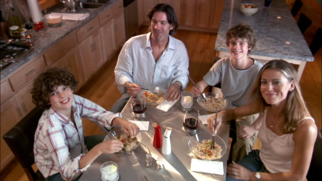 High angle portrait family eating stir-fry at kitchen table/ Green Bay, Wisconsin
