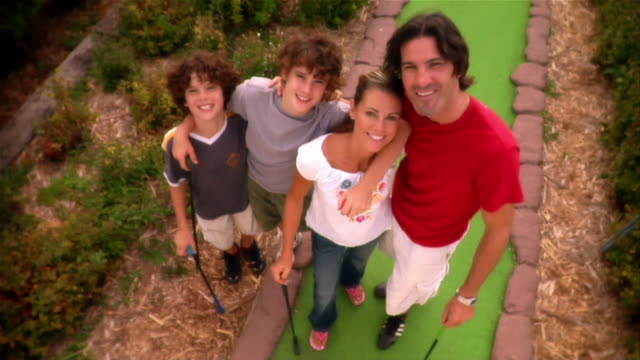 high angle portrait of family smiling up at camera from mini golf course fairway - minigolf stock-videos und b-roll-filmmaterial