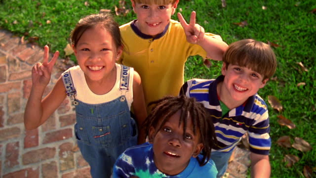 high angle MS PORTRAIT spinning zoom out Asian girl, Black boy + two blonde boys giving peace sign