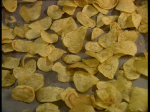 vídeos de stock, filmes e b-roll de cu high angle, potato chips being shaken along conveyor - snack salgado