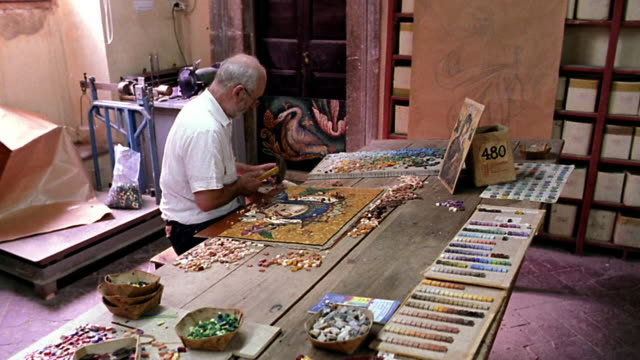 high angle profile man sitting at table putting tiles into mosaic in studio / italy - tile stock videos & royalty-free footage