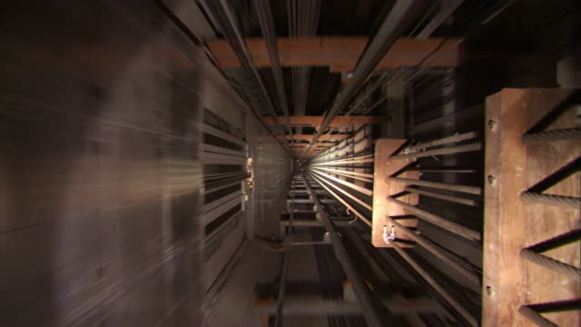 high angle push-in - an elevator travels through a long shaft. / shanghai, china - fahrstuhlperspektive stock-videos und b-roll-filmmaterial