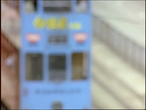 high angle rack focus of 2 double decker trolleys passing on hong kong street - 1997 stock-videos und b-roll-filmmaterial