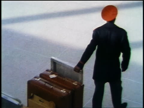 vidéos et rushes de 1957 high angle rear view black male porter pulling cart full of luggage - valise