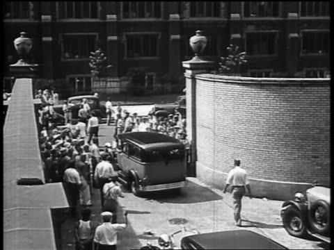 b/w 1934 high angle rear view car bearing casket with john dillinger exiting through gate crowd of onlookers - john dillinger stock-videos und b-roll-filmmaterial